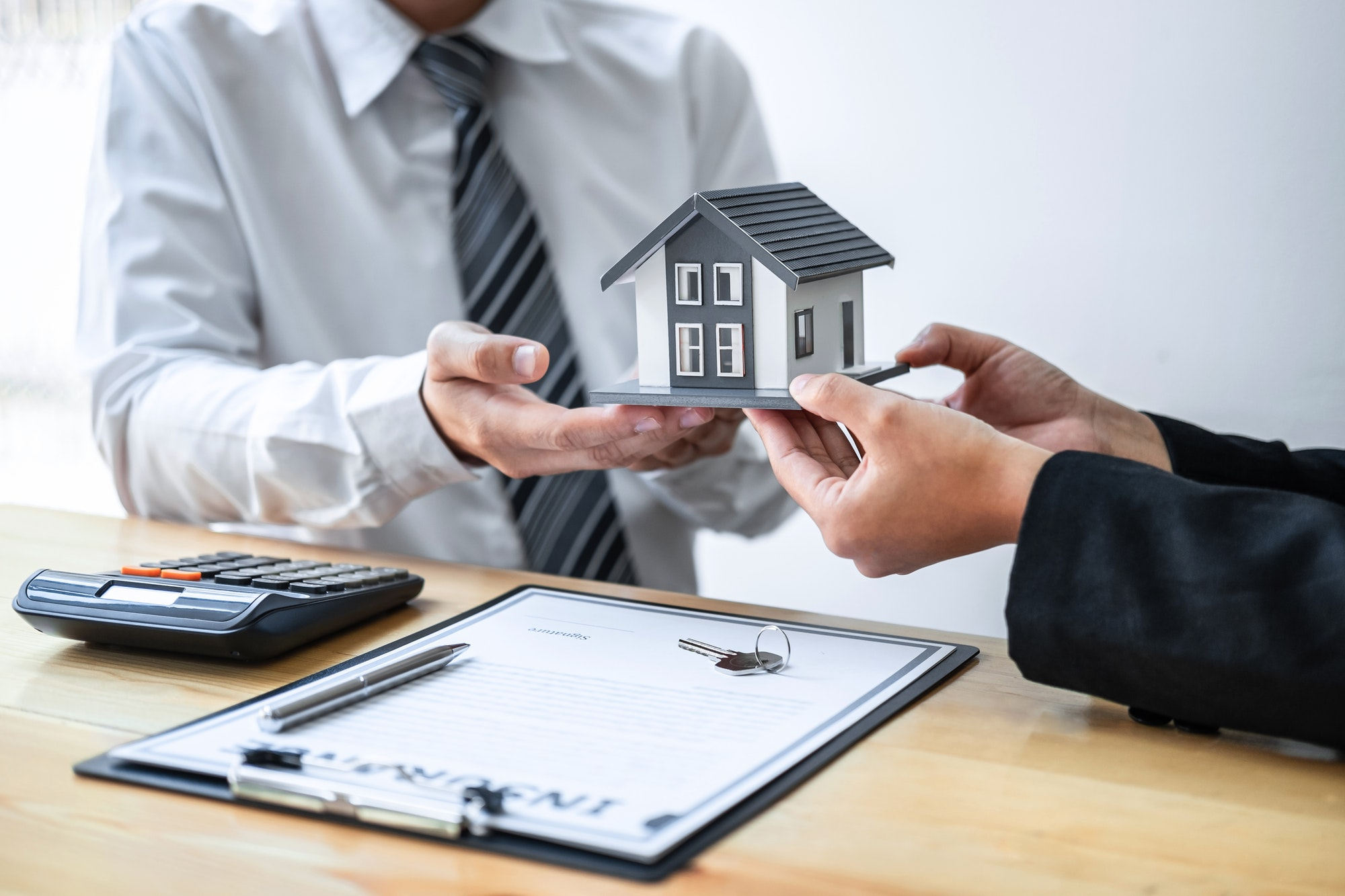 Estate agent are presenting home loan and giving house to client after discussing and signing