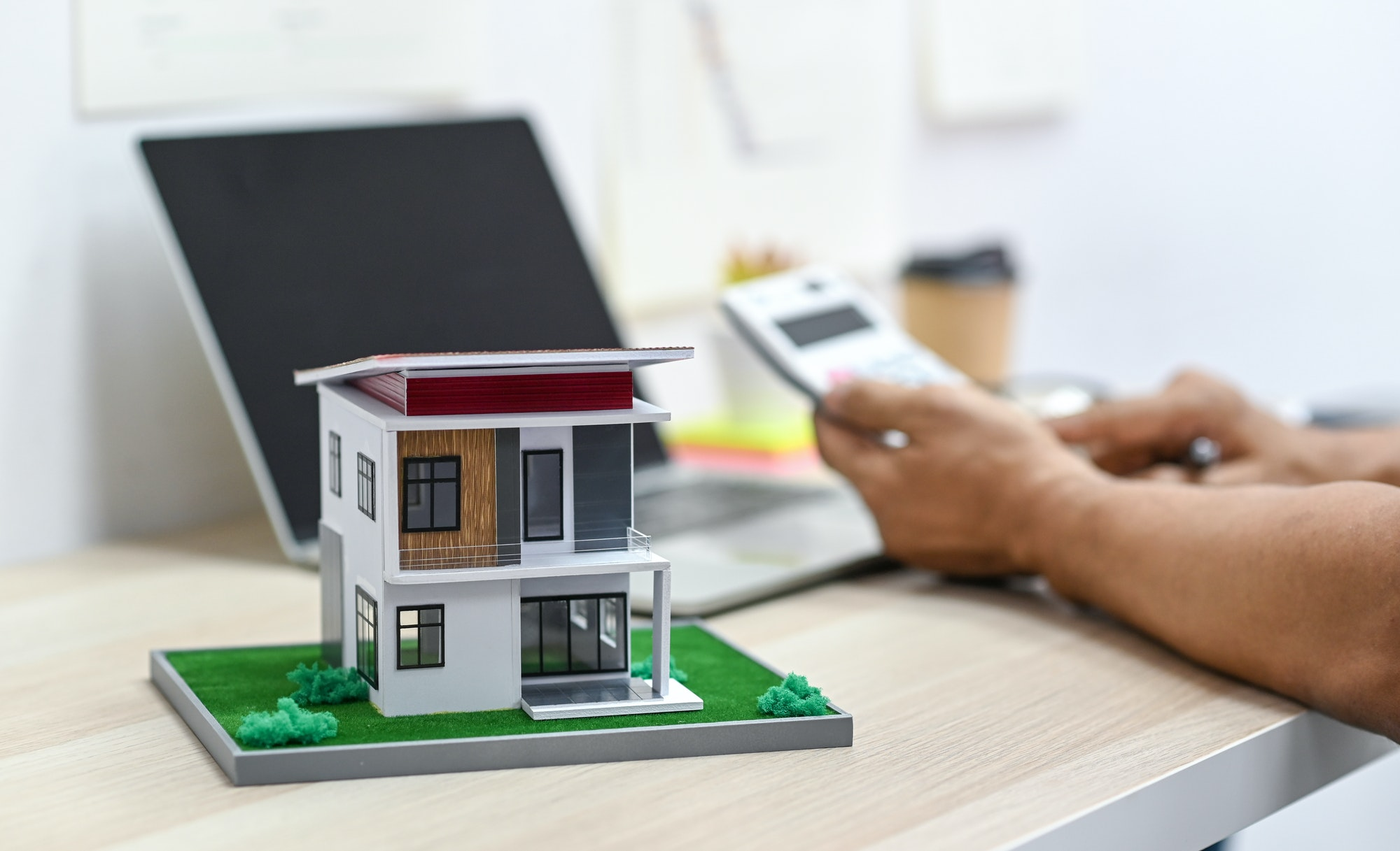 Model house on a table with blurry a person background using calculator and a laptop on the table.